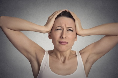 overwhelmed: Closeup portrait stressed sad young woman overwhelmed having headache about to cry, hands on head Stock Photo