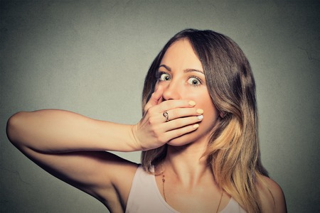 hands on mouth: Portrait of scared young woman covering with hand her mouth isolated on gray wall background