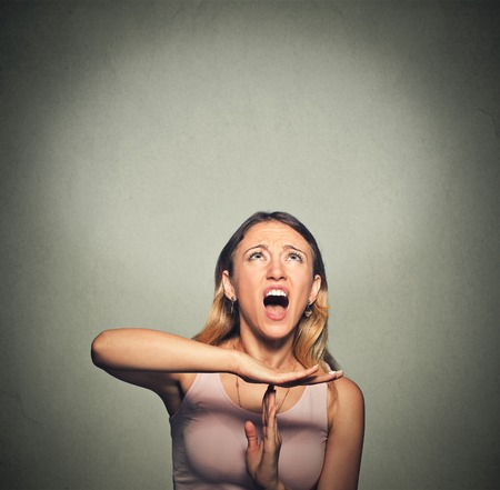 stop time: Young woman showing time out hand gesture, frustrated screaming to stop isolated on grey wall background.