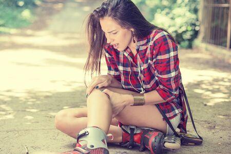 dolor: patinaje en línea herido mujer joven que sufre de dolor sentado en el suelo tocando rodilla dolorosa espera en necesidad de ayuda médica al aire libre en día de verano