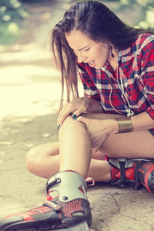 rollerskates: in-line skating injured young woman suffering from pain sitting on the ground touching painful knee waiting in need for medical help outdoors on summer day