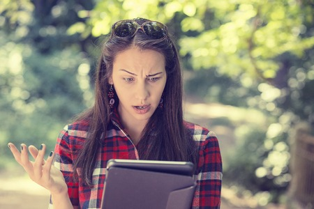 Portrait upset sad skeptical unhappy serious woman using mobile pad computer displeased with email news she received isolated park trees background.  Stockfoto