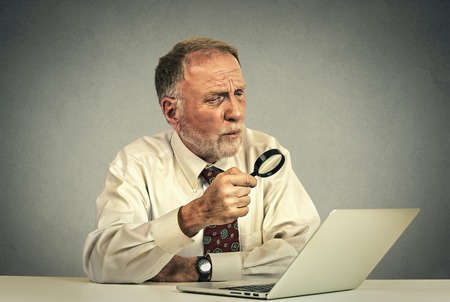 confundido: Retrato del hombre mayor que trabaja el investigador mirando a través de lupa en la pantalla del portátil aislados sobre fondo gris de la pared. Foto de archivo