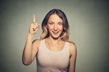 aha: Portrait happy beautiful excited woman pointing with finger up isolated on grey wall background.