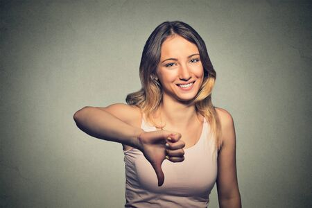 desprecio: Retrato del primer mujer que muestra los pulgares abajo firma sarcásticos gesto de la mano feliz a alguien hecha error perdido fallado aislado sobre fondo gris de la pared.