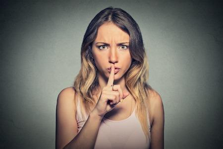 guardar silencio: Retrato de la mujer hermosa con el dedo en los labios aislados en fondo gris