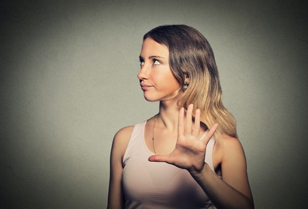 giving: Closeup portrait young annoyed angry woman with bad attitude giving talk to hand gesture with palm outward isolated grey wall background.  Stock Photo