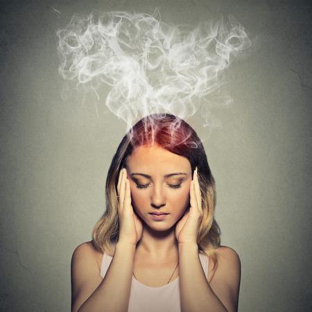 Portret jonge beklemtoonde vrouw denken te hard stoom uit up van het hoofd die op grijze muur achtergrond. Stockfoto
