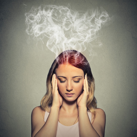 Portrait young stressed woman thinking too hard steam coming out up of head isolated on grey wall background.  Foto de archivo