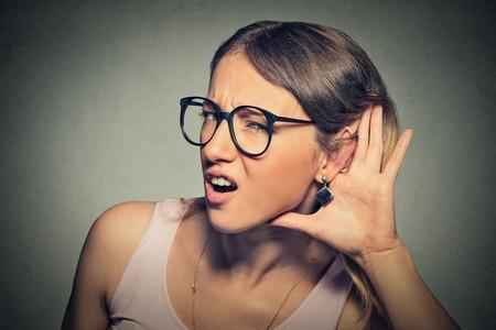 oir: Retrato del primer joven mano mujer entrometida a oreja gesto tratando cuidadosamente en secreto con atención escuchar en las noticias jugosa conversación chisme aislado fondo gris.