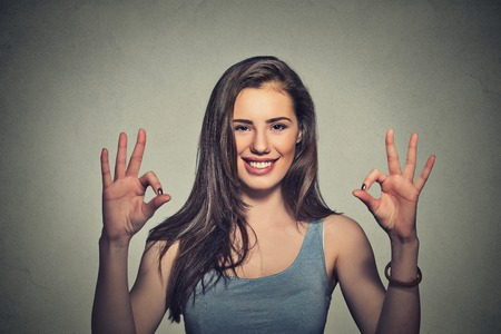 ok sign: Excited happy young optimistic woman giving ok sign gesture with two hands isolated on gray wall background.  Stock Photo