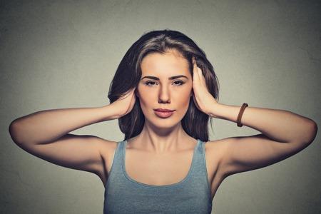 guardar silencio: Retrato de joven y atractiva mujer casual que cubre con las manos sus ojos oídos abrió aislado sobre fondo gris de la pared. Foto de archivo
