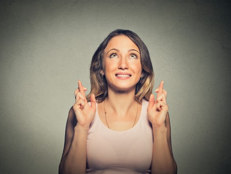 hope concept: Closeup portrait hopeful beautiful woman crossing her fingers looking up hoping, asking best isolated on gray wall background. Human face expression, emotions, feeling attitude reaction