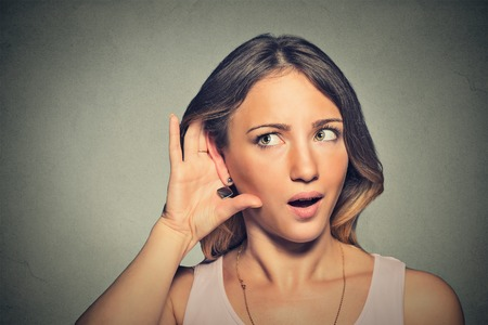 isolated on gray: Closeup portrait surprised young nosy woman hand to ear gesture carefully intently secretly listening juicy gossip conversation news isolated gray wall background. Human face expression emotion