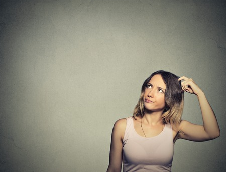 memories: Closeup portrait headshot young woman scratching head, thinking daydreaming deeply about something looking up isolated on gray wall background. Human facial expression emotion feeling sign symbol