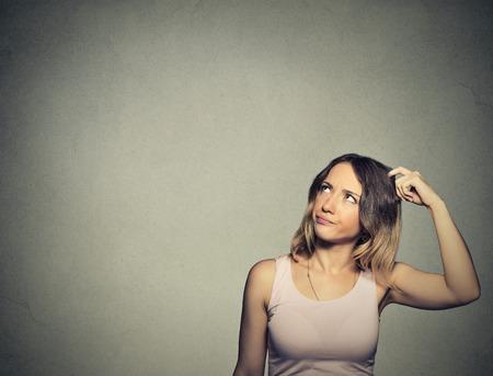 reflexionando: Headshot Retrato del primer mujer joven rascarse la cabeza, pensando so�ando profundamente en algo mirando hacia arriba aislados en el fondo gris de la pared. Humano facial emoci�n expresi�n sentimiento s�mbolo Foto de archivo