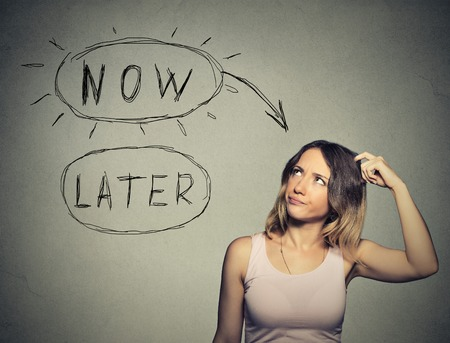 Now or later. Woman thinking scratching head looking up isolated on grey wall background. Human face expression