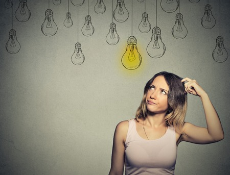 above head: Portrait thinking woman looking up with light idea bulb above head isolated on gray background