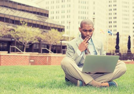 hombres de negro: Hombre de negocios joven que se sienta en un césped fuera de la oficina corporativa de trabajo en el ordenador portátil Foto de archivo
