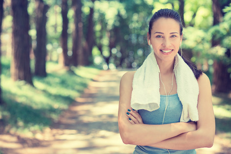 Portrait young attractive smiling fit woman with white towel resting after workout sport exercises outdoors on a background of park trees. Stock Photo