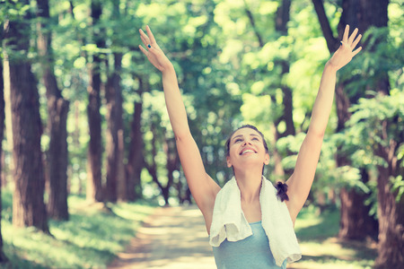 deep: Young fit woman arms raised up to sky celebrating freedom.
