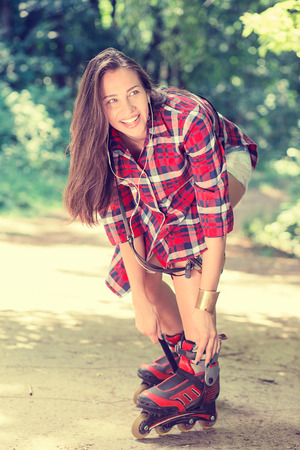 inline skater: Girl going rollerblading sitting putting on in line skates outdoors on summer day in park. Woman in outdoor activities concept