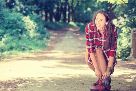 woman work: Girl going rollerblading sitting putting on in line skates outdoors on summer day in park. Woman in outdoor activities concept