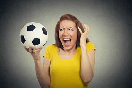 pissed off: Angry frustrated woman screaming at soccer ball