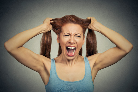 Portrait of a very angry woman screaming acting out Stock Photo