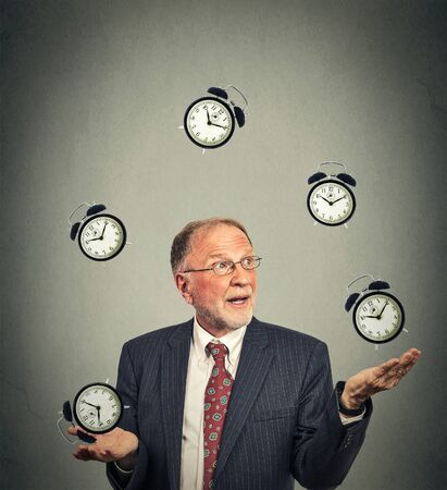 organize: Portrait senior business man in suit juggling multiple alarm clocks isolated on gray office wall background. Timing concept