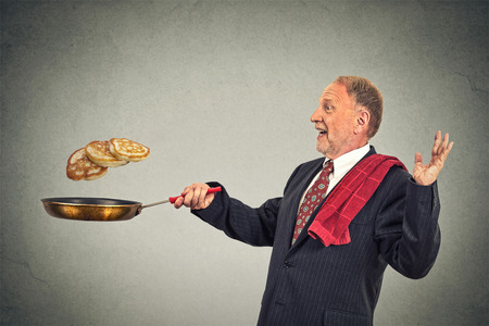culinary skills: Happy smiling senior man tossing pancakes on frying pan isolated on gray wall background. Positive face expression emotion, Kitchen fun concept Stock Photo