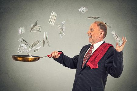 make money: Happy senior elderly business man juggling money dollar bills banknotes isolated on grey wall background