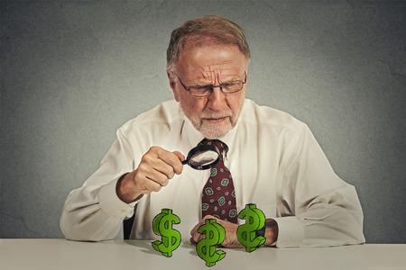 business skeptical: Hombre de negocios mayor esc�ptica mirando a trav�s de la lupa en el signo de d�lar s�mbolo aislado fondo gris.