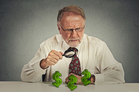 invest: Senior skeptical business man looking through magnifying glass at dollar sign symbol isolated gray background. Stock Photo