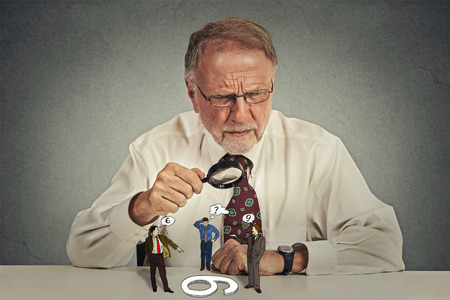isolated on gray: Senior business man with glasses sitting at desk skeptically looking at group arguing people through magnifying glass isolated gray wall background.