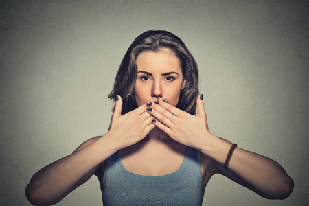 hand in mouth: Closeup portrait of young woman covering with hands her mouth isolated on gray wall background