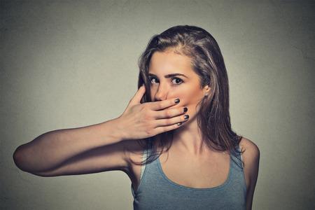 boca: Retrato de mujer joven asustado que cubre con la mano la boca aislado en el fondo gris de la pared Foto de archivo