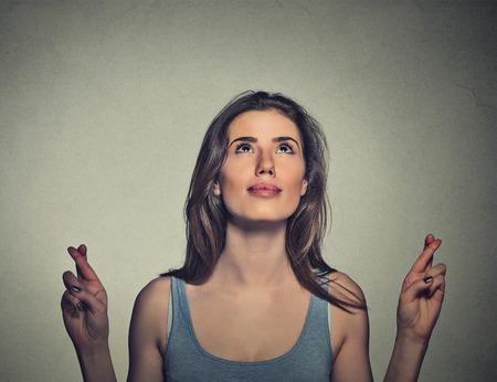 クローズ アップ肖像画希望に満ちた美しい若い女性希望を探している彼女の指を交差