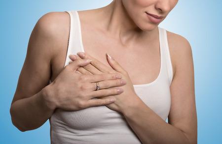 seni: Closeup ritagliata ritratto giovane donna con il dolore al seno petto toccando colorato isolato su sfondo blu