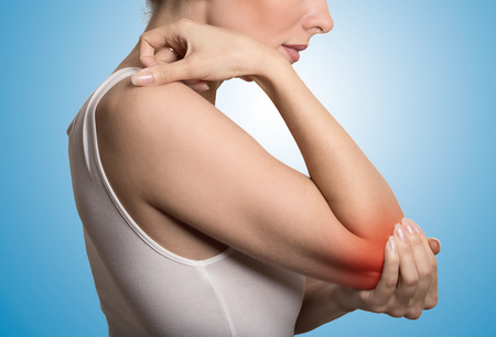 Joint inflammation indicated with red spot on females elbow. Arm pain and injury concept. Closeup cropped portrait woman with painful elbow isolated on blue background