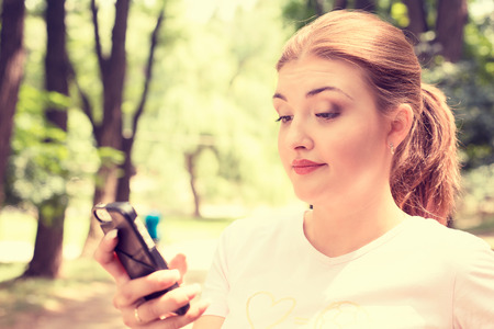 Closeup portrait upset skeptical unhappy serious woman talking texting on phone displeased with conversation isolated park trees outdoors background.