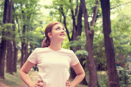 Portrait young attractive smiling fit woman resting after workout sport exercises outdoor looking up enjoying fresh air standing on background park trees. Healthy lifestyle well being wellness concept