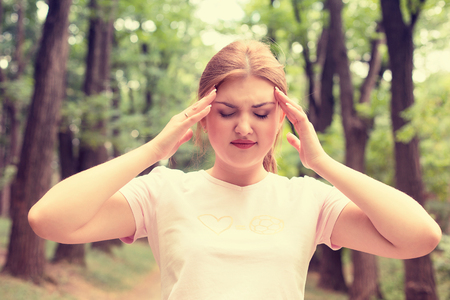 psychology: portrait stressed sad young woman standing outdoors on summer day in park