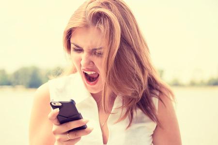 mujer enojada: Retrato enojado joven gritando en el teléfono móvil fuera de pie con la ciudad de fondo. Las emociones negativas sentimientos