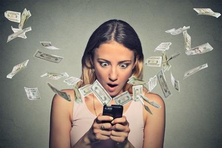 pieniądze: Technologia bankowości online przelew, e-commerce. Zszokowany młoda kobieta za pomocą smartfona z banknotów dolarowych latających poza ekran samodzielnie na szarym tle ściany biurowych. Zdjęcie Seryjne