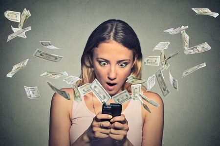 of champions: Technology online banking money transfer, e-commerce concept. Shocked young woman using smartphone with dollar bills flying away from screen isolated on gray wall office background.