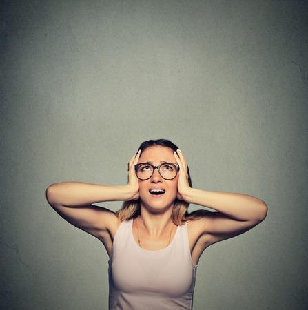 ruido: Retrato joven molesto, triste, mujer tensionada que cubre las orejas, mirando hacia arriba, por decir, dejar de hacer ruido fuerte, y me da dolor de cabeza aislado en el fondo gris con espacio de copia. reacci�n emoci�n negativa