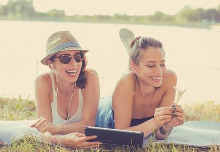 riendo: Dos divertidos felices mujeres jóvenes amigos riendo navegación viendo videos de medios sociales blogs escuchar música en el ordenador cojín inteligente que pone al aire libre en la pradera verde en día soleado de verano