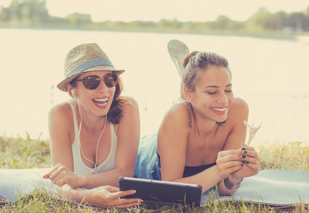 best group: Two funny happy young women friends laughing browsing watching social media videos blogs listen to music on smart pad computer laying outdoors on green meadow on sunny summer day Stock Photo