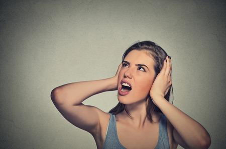 oreja: Retrato del primer joven mujer estresada infeliz que cubre sus o�dos buscar parada haciendo ruido fuerte que me est� dando dolor de cabeza aislado sobre fondo gris de la pared. La emoci�n negativa sensaci�n expresi�n de la cara